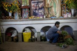 A man from Teotitlán del Valle preparing the Day of the Dead altar in his home in Teotitlán del Valle