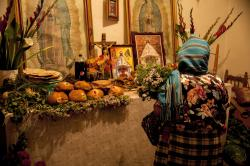 A woman in Teotitlán del Valle presenting her offerings at the Day of the Dead altar in a relative's home.