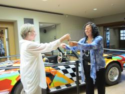Dr. Sackler handing car keys over to Della Warrior