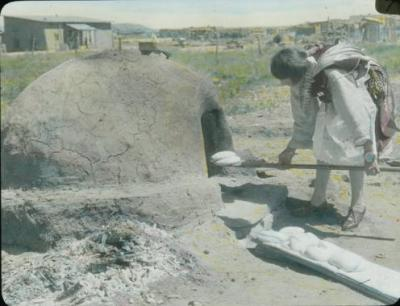 Pueblo woman baking bread in horno oven, New Mexico, unknown photographer (circa 1915). Palace of the Governors Photo Archive LS.1722, New Mexico History Museum, Santa Fe