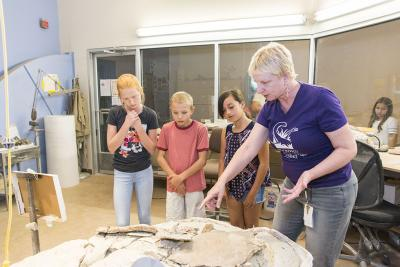 Museum Educator Deb Novak explains a specific fossil to students in the Musem's Fossilworks.  Photo: Caitlin Jenkins