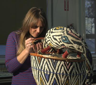 Conservator Sophie Hunter repairs bead work on a ceremonial mask for Beadwork