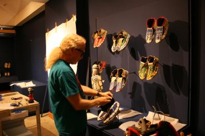 Preparator Paul Singdahlsen installs beaded moccasins in Stepping Out.
