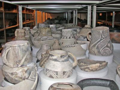 : 800 year old, pre-contact bowls and jars from the Museum of Indian Arts & Culture collections, densely packed onto shelves in their current storage room.  Photo by: Julia Clifton. Courtesy of the Museum of Indian Arts & Culture