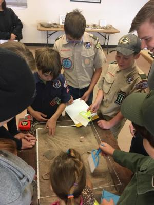 11-LOA - 2018 A troop of Boy Scouts learning how to excavate and record archaeological discoveries in MIAC's Dig Box. Photographer: Amy Montoya. Photo Courtesy of Museum of Indian Arts & Culture