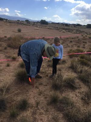 11-LOA-2018 MIAC Research Associate Leon Natker assists a young visitor is finding artifacts on the survey course designed to teach visitors the importance of recording artifact locations and the difficulty of recording surface collections. Photographer: