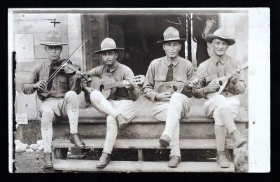 Servando Gonzales (left, with violin) and fellow musicians, ca. 1919 - Private Servando Gonzales, of Tijeras, played the violin with other musicians in his division, the 19th Infantry, Company E.  New Mexico Council of Defense. World War I, Series 18.1. N