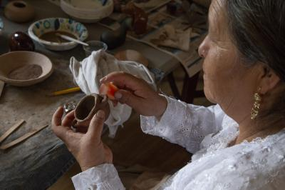2-MOIFA-Gallery of Conscience  Adelina Garcia with her clay pig piece during a healing pottery workshop at Elder Kathy Wan Povi Sanchez' house, San Ildefonso Pueblo, April 10th, 2018    Photographer: Chloe Accardi