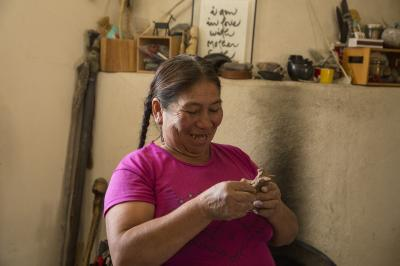 2-MOIFA-Gallery of Conscience:Rosalia Tineo polishing  er clay piece during a healing pottery workshop at Elder Kathy Wan Povi Sanchez' house, San Ildefonso Pueblo, April 10th, 2018    Photographer: Chloe Accardi