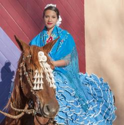 Alexina García Chávez rides side saddle on top of Poesía in the manner of the feria de abril (April Fair).