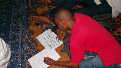 Fulani Student in Conakry, Guinea studies the ADLaM alphabet.