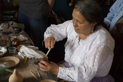 2-MOIFA-Gallery of Conscience Adelina Garcia with clay pig piece during a healing pottery workshop at Elder Kathy Wan Povi Sanchez' house, San Ildefonso Pueblo, April 10th, 2018  Photographer: Chloe Accardi